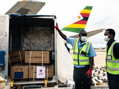 TOPSHOT - Workers offload part of a consignment of 200,000 doses of the Sinopharm coronavirus vaccine from China off an Air Zimbabwe aeroplane which has just landed on February 15, 2021 at the Robert Mugabe International Airport. (Photo by Jekesai NJIKIZANA / AFP) / The erroneous mention[s] appearing in the …