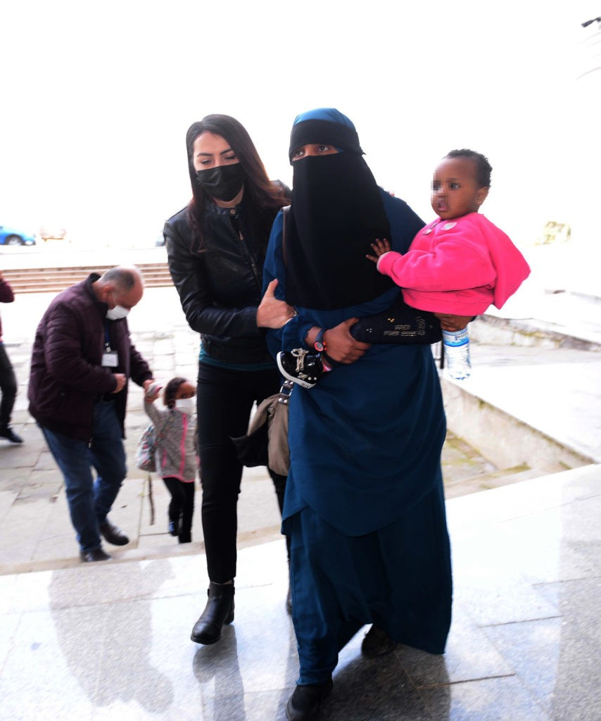 A handout picture taken on February 15, 2021 shows a 26-year-old woman (R), who had held New Zealand and Australian citizenships, and her two children escorted by Turkish plain clothes police officers after trying to enter Turkey illegally from Syria at Reyhanli district in Hatay. - New Zealand Prime Minister Jacinda Ardern angrily accused Australia on February 16, 2021 of shirking its responsibility for a dual national arrested in Turkey with alleged links to the Islamic State militant group. The 40-year-old leader said Australia had abdicated its responsibilities by unilaterally cancelling the citizenship, forcing New Zealand to shoulder the responsibility for the woman, who has not lived in New Zealand since she was 6. (Photo by IZZET NAZLI / Demiroren News Agency (DHA) / AFP) (Photo by IZZET NAZLI/Demiroren News Agency (DHA)/AFP via Getty Images)