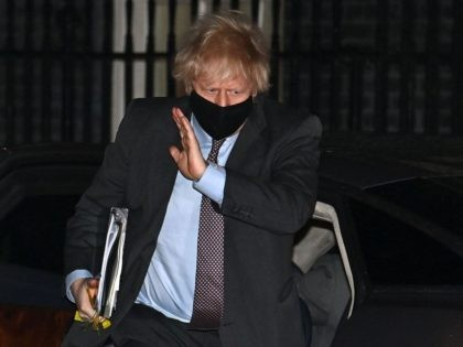 Britain's Prime Minister Boris Johnson, waring a face covering, returns to 10 Downing Street in central London after making a statement to Parliament on the government's roadmap out of lockdown on February 22, 2021. - The UK government on Monday set out a four-step plan to ease coronavirus restrictions, expressing …
