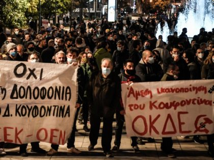 "Leftist protesters hold a banner reading ""No to the murder of Dimitris Koufodinas"" (L) during a demonstration in Athens on February 24, 2021, held in support to a jailed far left group member on hunger strike since 48 days. - Dimitris Koufodinas, 62, has been in intensive care since last …"