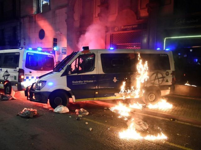"""A Molotov cocktail bursts into flames next to a municipal police vehicle during a demonstration for various social issues under the slogan """"Fight, Create Popular Power"""" including the recent arrest of Spanish rapper Pablo Hasel in Barcelona on February 27, 2021. (Photo by Josep LAGO / AFP) (Photo by JOSEP …"""