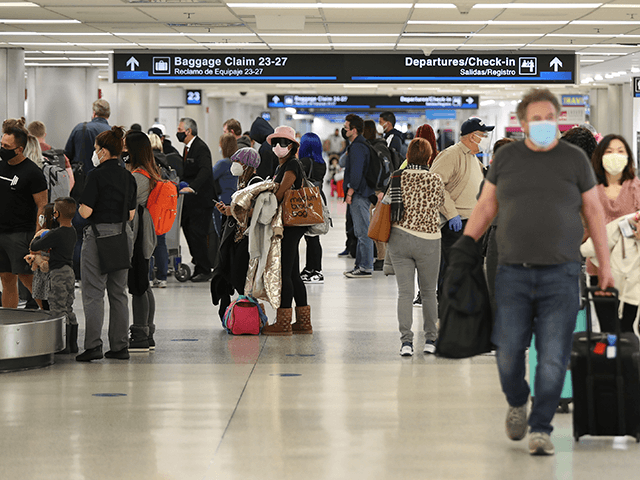 People gather their luggage after arriving at Miami International Airport on a plane from New York on February 01, 2021 in Miami, Florida. An executive order signed by U.S. President Joe Biden last week mandates mask-wearing on federal property and on public transportation as part of his plan to combat …