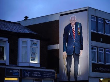 SOUTHPORT, ENGLAND - FEBRUARY 03: A mural of Captain Sir Tom Moore, by artist Robert Newbiggin, adorns a wall on February 03, 2021 in Southport, England. WWII veteran, Sir Tom had raised nearly £33 million for NHS charities ahead of his 100th birthday last year by walking laps of his …