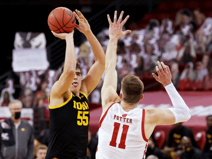 Luka Garza #55 of the Iowa Hawkeyes attempts a shot while being guarded by Micah Potter #11 of the Wisconsin Badgers in the first half at the Kohl Center on February 18, 2021 in Madison, Wisconsin. (Photo by Dylan Buell/Getty Images)