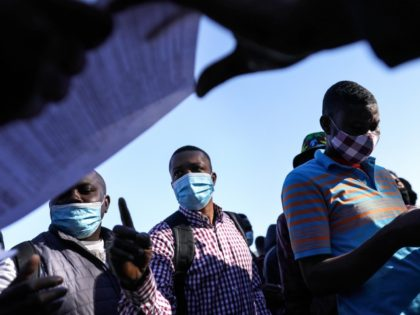 TIJUANA, MEXICO - FEBRUARY 19: People from Haiti who are seeking asylum in the United States wait for flyers explaining updated asylum policies outside the El Chaparral border crossing on February 19, 2021 in Tijuana, Mexico. Those seeking asylum have been waiting months and years in Tijuana and other locations …