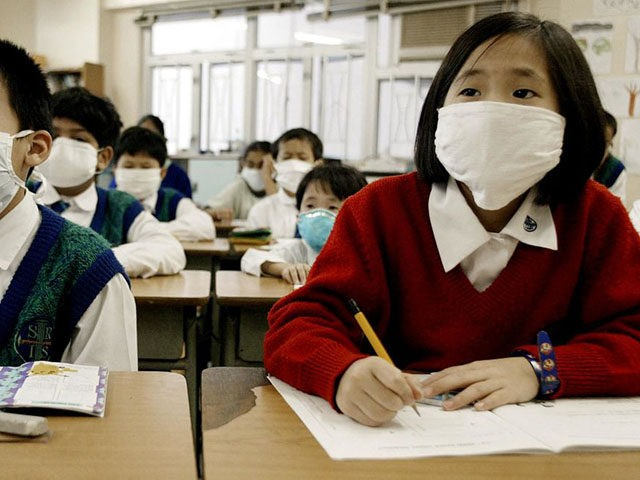 Hong Kong school children wear masks in class to protect against a killer outbreak of pneumonia which shows no sign of abating in the territory 28 March 2003. The disease known as Severe Acute Respiratory Syndrome (SARS) is sowing fear in Hong Kong with the authority's ordering all kindergartens, primary …
