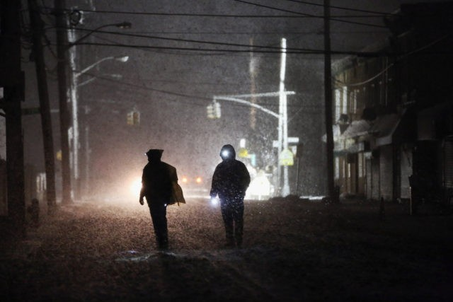 NEW YORK, NY - NOVEMBER 07: People walk through a darkened street using flashlights as a police spotlight shines behind them during a Nor'Easter snowstorm in the Rockaway neighborhood on November 7, 2012 in the Queens borough of New York City. The Rockaway Peninsula was especially hard hit by Superstorm …