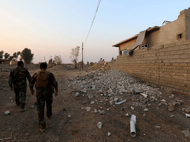 Peshmerga fighters walk past a damaged house in an Iraqi Kurdish Kakai minority village located near the town of Kalak, east of Mosul, on October 26, 2016, after Iraqi forces recaptured it from Islamic State (IS) group jihadists a few months ago. The Kakai are a secretive religious minority that …