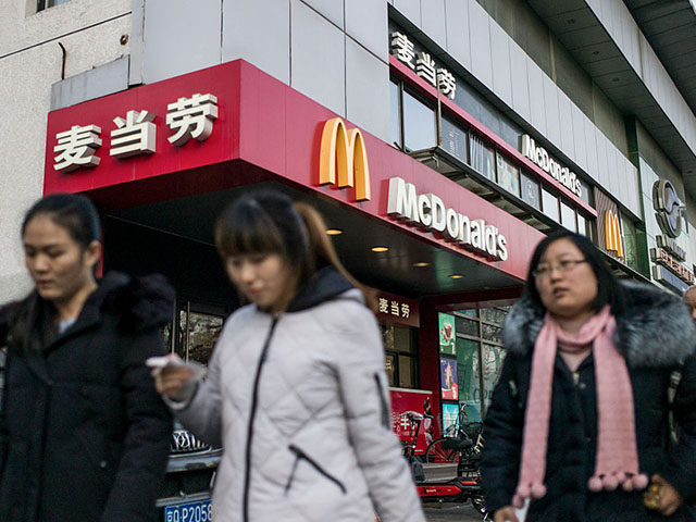 People walk past a McDonald's fast food restaurant in Beijing on January 9, 2017.