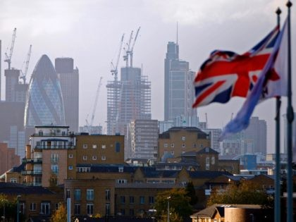 "A Union flag flies from a pole as construction cranes stand near skyscrapers in the City of London, including the Heron Tower, Tower 42, 30 St Mary Axe commonly called the ""Gherkin"", the Leadenhall Building, commonly called the ""Cheesegrater"", as they are pictured beyond blocks of residential flats and apartment …"