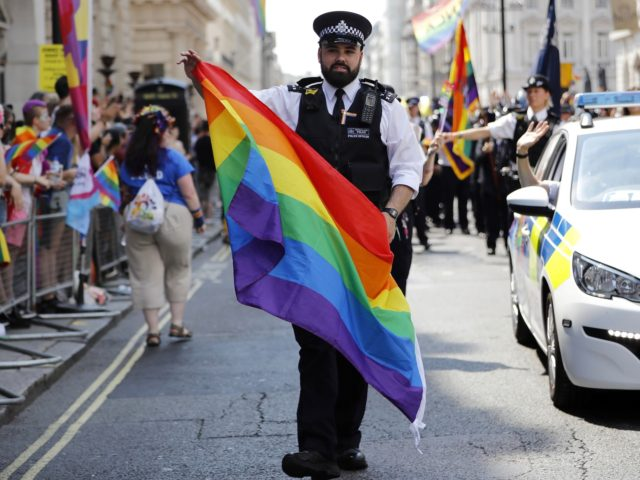 Police officers join supporters and members of the Lesbian, Gay, Bisexual and Transgender (LGBT) community taking part in the annual Pride Parade in London on July 7, 2018. (Photo by Tolga AKMEN / AFP) (Photo credit should read TOLGA AKMEN/AFP via Getty Images)