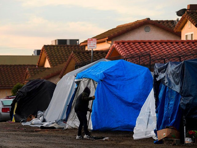 People experiencing homelessness clean the area around their tent shelters before a Los Angeles City Bureau of Sanitation cleanup sweep of homeless encampments in the area during the Covid-19 pandemic on January 28, 2021 in the Harbor City neighborhood of Los Angeles. - Community activists with Services Not Sweeps monitored …