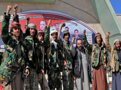 Fighters loyal to Yemen's Huthi rebels raise their fists and chant slogans as they visit the grave of slain Huthi political leader Saleh al-Sammad at al-Sabeen square in the capital Sanaa, on January 11, 2021. - In April 2018, al-Sammad, who was on the Saudi-led coalition's wanted list, was killed …