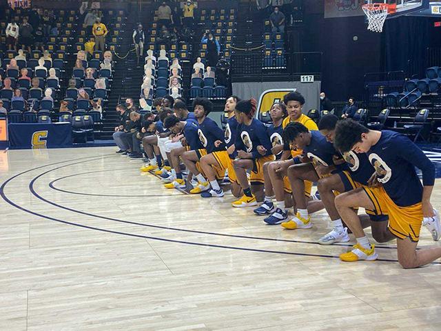 ETSU basketball player kneel