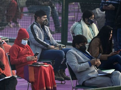 Spectators wearing facemasks use their mobile phones as they wait for the start of the Republic Day Parade in New Delhi on January 26, 2021. (Photo by Jewel SAMAD / AFP) (Photo by JEWEL SAMAD/AFP via Getty Images)