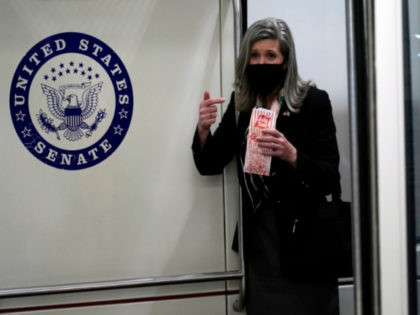 Sen. Joni Ernst, R-Iowa, holds popcorn as she rides the Senate subway on Capitol Hill in Washington, Thursday, Feb. 11, 2021, after the third day of the second impeachment trial of former President Donald Trump. (AP Photo/Susan Walsh)