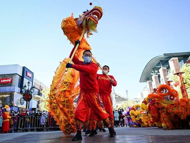 A dragon dance team perform outside a mall in Beijing on February 16, 2021, on the fifth day of the Lunar New Year, which ushered in the Year of the Ox on February 12. (Photo by WANG Zhao / AFP) (Photo by WANG ZHAO/AFP via Getty Images)