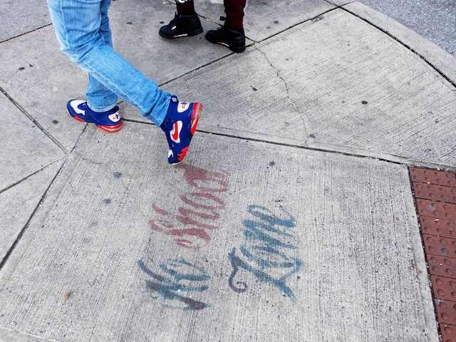 "In this file photo, two men walk past a sign spray painted on the sidewalk stating ""No Shoot Zone"" in Baltimore, MD, on December 17, 2018. (Jim Watson/AFP via Getty Images)"