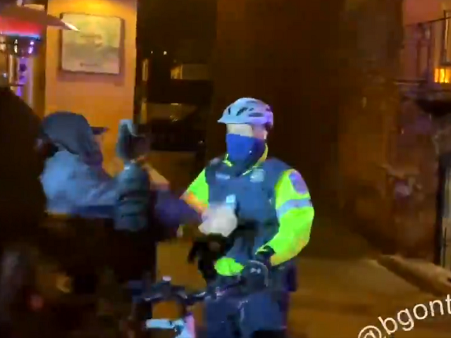 Protester wearing black bloc strikes a DC Police Officer. (Twitter Video Screenshot: @BGOnTheScene)