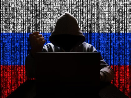 Russian hacker in the hood threatens with his fist against the backdrop of a tricolor from a binary code, cyber threat