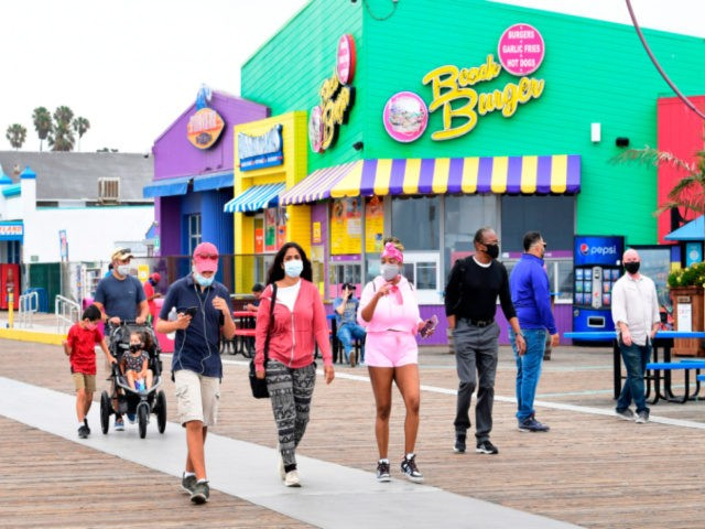 People wearing facemasks visit Santa Monica Pier which re-opened on June 25 after closure for over three months due to the coronavirus pandemic, on June 26, 2020 in Santa Monica, California. - A gradual re-opening of businesses continues across the state, despite a continued rise in coronavirus cases. (Photo by …