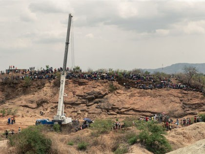 Curious onlookers sitting on a hill watch closely as rescue workers busy at work installing a water pump to drain water from a mine shaft so that they can gain access to at least 40 informal gold miners trapped inside a collapsed shaft at Ran Mine in Bindura, on November …