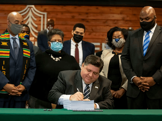 Flanked by lawmakers and supporters, Gov. J.B. Pritzker signs a sweeping criminal justice reform bill into law during a ceremony at Chicago State University, Monday, Feb. 22, 2021. (Brian Cassella/Chicago Tribune)/Chicago Tribune via AP)