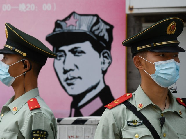 Paramilitary police officers stand guard in front of a poster of late communist leader Mao Zedong on a street south of the Great Hall of the People during the opening session of the National People's Congress (NPC) in Beijing on May 22, 2020. - China moved to impose stringent new …