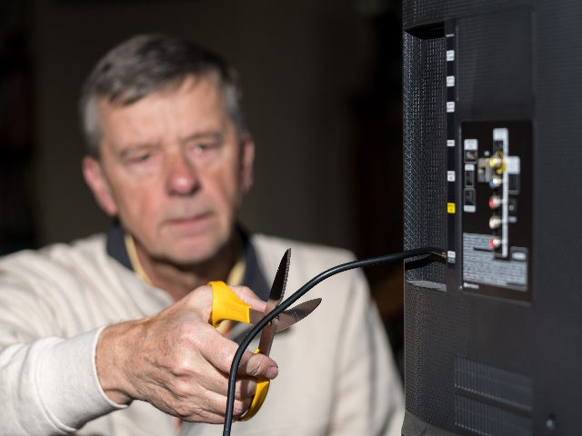 Senior man cutting the cord on his cable TV package - stock photo Close up of senior caucasian retired man cutting the aerial connection to his TV to illustrate cutting the cord