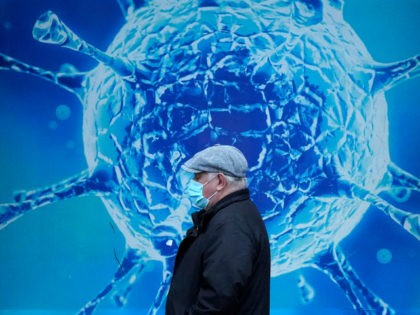 OLDHAM, UNITED KINGDOM - NOVEMBER 24: A man wearing a protective face mask walks past an illustration of a virus outside Oldham Regional Science Centre on November 24, 2020 in Oldham, United Kingdom. England is continuing its second national coronavirus lockdown. People are still permitted to exercise with one other …