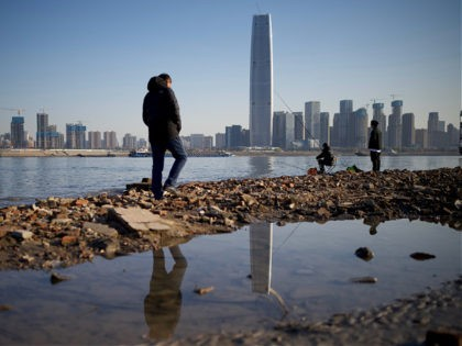 People walk along the banks of the Yangtze River on New Year's Eve day in Wuhan in Chinas central Hubei province on December 31, 2020. (Photo by Noel Celis / AFP) (Photo by NOEL CELIS/AFP via Getty Images)