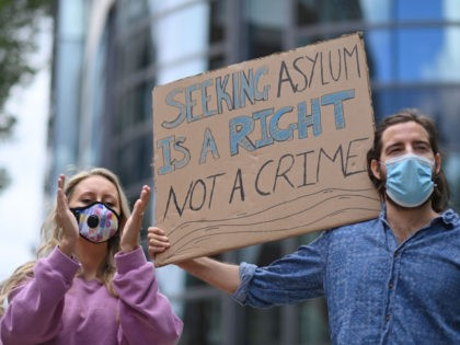 Protesters carry a placard at a demonstration to highlight conditions inside Brook House immigration removal centre, outside the Home Office in London on August 23, 2020. - Migrants who crossed the Channel to the UK are on hunger strike in a detention centre as they face deportation next week, according …