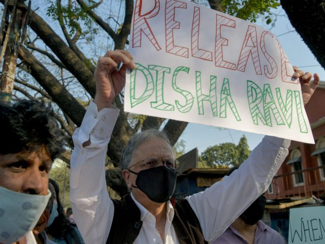 Historian, author and activist Ramachandra Guha (R) and various human rights organisation stage a demonstration against the arrest of the activist Disha Ravi by Delhi police for her alleged involvement with the violence during the farmers protest on India's Republic Day, in Bangalore on February 15, 2021. (Photo by Manjunath …