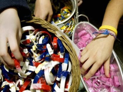 """Children browse through multi-colored bracelets 22 December 2004 at a clothing store in the Washington suburb of Rockville, Maryland. Following the yellow bracelet """"LiveStrong"""" campaign for cancer research of US cyclist Lance Armstrong, several other causes have put various colored bracelets on the market, while others have taken the ride …"""