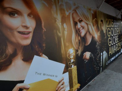 Commuters walk past a poster showing the Golden Globe Award hosts Tina Fey (L) and Amy Poehler (R) in Beverly Hills on January 9, 2015. The comic duo will present the Globes for a third and final year, in what organizers hope will continue its ratings winning streak. Last year …