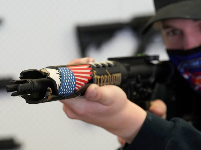 A customer looks at a custom made AR-15 style rifle at Davidson Defense in Orem, Utah on February 4, 2021. - Gun merchants sold more than 2 million firearms in January, a 75% increase over the estimated 1.2 million guns sold in January 2020, according to the National Shooting Sports …