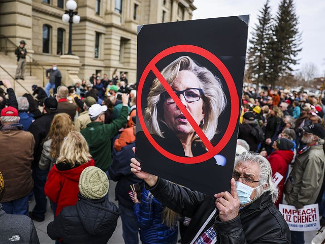 CHEYENNE, WY - JANUARY 28: A man holds up a sign against Rep. Liz Cheney (R-WY) as Rep. Matt Gaetz (R-FL) speaks to a crowd during a rally against her on January 28, 2021 in Cheyenne, Wyoming. Gaetz added his voice to a growing effort to vote Cheney out of …