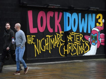 "Pedestrians walk past graffiti reading ""Lockdown 3: The Nightmare after Christmas"" painted on a boarded up restaurant passes a Government Covid-19 information poster near a road in Manchester, northern England, on February 15, 2021. - Britain intends to seek a ""cautious but irreversible"" ending of strict coronavirus restrictions, Prime Minister …"