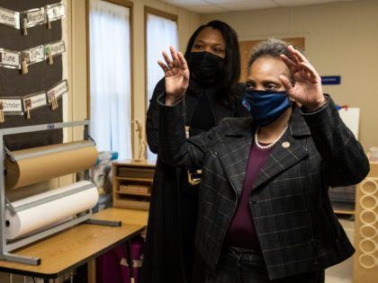 Mayor Lori Lightfoot, right, and Chicago Public Schools CEO Janice Jackson wave to preschool students who did not come to class in person but are learning virtually at at Dawes Elementary School in Chicago, Monday, Jan. 11, 2021. Monday was the first day of optional in-person learning for preschoolers and …