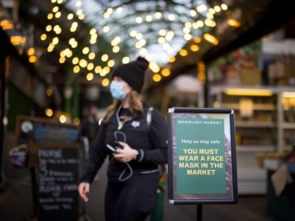A sign informs people that it is mandatory to wear face masks at Borough Market in London on January 12, 2021. - Borough market, an open-air market popular with tourists and Londoners alike, has required customers and stall-holders to wear masks since January 11 as a measure to keep the …