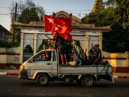 YANGON, MYANMAR - FEBRUARY 09: Protesters waving red flags make three-finger salutes while riding on the back of a pickup truck on February 09, 2021 in Yangon, Myanmar. Myanmar declared martial law in parts of the country, including its two largest cities, as massive protests continued to draw people to …
