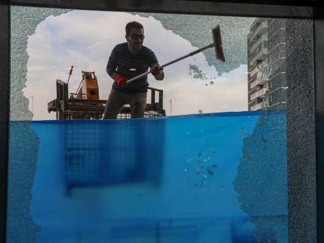 A worker cleans shattered glass on February 16, 2021 outside a damaged shop following a rocket attack the previous night in Arbil, the capital of the northern Iraqi Kurdish autonomous region. - The United Nations warned Iraq could spin out of control after a rocket attack on the Kurdish regional …