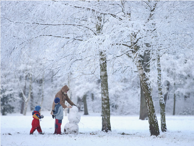 BERLIN, GERMANY - DECEMBER 26: A mother and two children build a snowman in a snow-covered park in Zehlendorf district during the season's first snowfall on December 26, 2014 in Berlin, Germany. Germany has so far experienced a very mild winter. (Photo by Sean Gallup/Getty Images)
