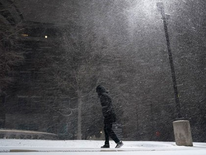 A woman walks through falling snow in San Antonio, Sunday, Feb. 14, 2021. Snow and ice blanketed large swaths of the U.S. on Sunday, prompting canceled flights, making driving perilous and reaching into areas as far south as Texas' Gulf Coast, where snow and sleet were expected overnight. (AP Photo/Eric …