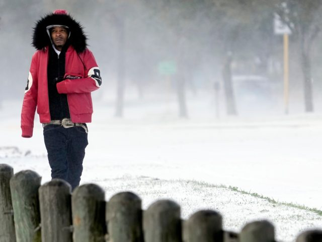 Igee Cummings walks through the snow Monday, Feb. 15, 2021, in Houston. A winter storm dropping snow and ice sent temperatures plunging across the southern Plains, prompting a power emergency in Texas a day after conditions canceled flights and impacted traffic across large swaths of the U.S. (AP Photo/David J. …