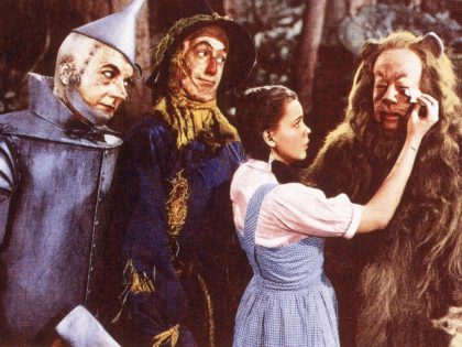 A lobby card from the film 'The Wizard Of Oz,' shows a film still of a scene in which American actress Judy Garland (1922 - 1969) (as Dorothy) wipes tears from the eyes of actor Bert Lahr (1895 - 1967) (as the Cowardly Lion), while watched by Jack Haley (1898 …