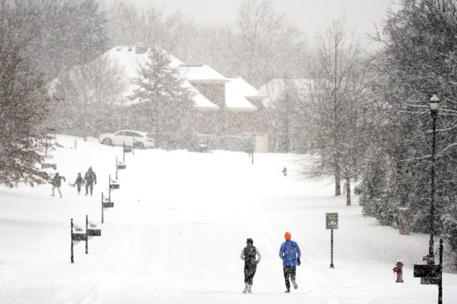 Joggers run down a street empty of cars Thursday, Feb. 18, 2021, in Nolensville, Tenn. A second winter storm in a week is bringing more snow to much of Tennessee. (AP Photo/Mark Humphrey)