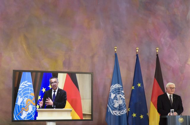 German President Frank-Walter Steinmeier, right, and Director General of the World Health Organization Tedros Adhanom Ghebreyesus, left on the screen, brief the media on a virtual joint news conference at Bellevue Palace in Berlin, Germany, Monday, Feb. 22, 2021. (AP Photo/Markus Schreiber)