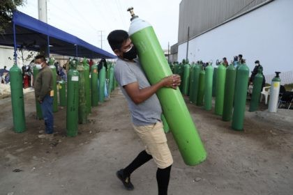 A man carries his empty oxygen tank to be filled after arriving at the head of the line, in the Villa El Salvador neighborhood of Lima, early Thursday morning, Feb. 18, 2021. A crisis over the supply of medical oxygen for coronavirus patients has struck in Africa and Latin America, …