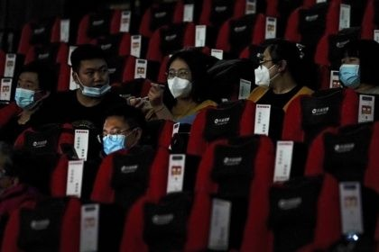 People wearing face masks to help curb the spread of the coronavirus chat each other as the watch a film at Poly Cinema in Beijing on Thursday, Feb. 25, 2021. With coronavirus well under control in China and cinemas running at half capacity, moviegoers are smashing China's box office records, …